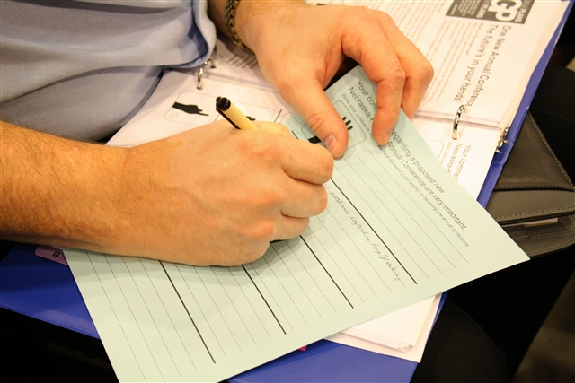 A conference member writes comments on the five-finger ballot.